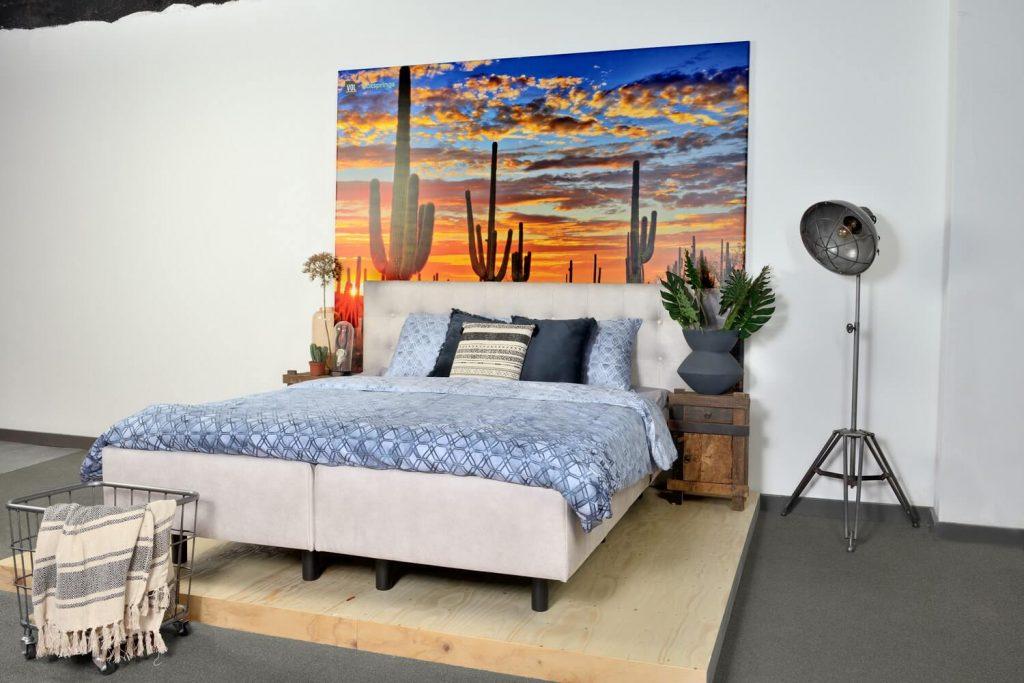 Zijaanzicht van een bed in de showroom bladel, in een lichte kleur met een samengevoegde box en matras