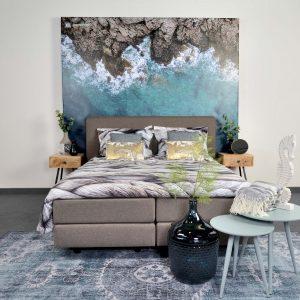 luxe boxspring bed met een blauwe zee achtergrond